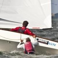 Ein Segler hilft seinem vom Boot gefallenen Teamkollegen