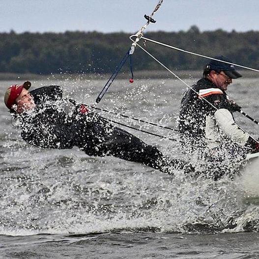 Ein Segelboot mit zwei Seglern. Ein Segler zeigt vollen Einsatz und lehnt sich nahezu waagerecht über die Steuerbordseite des Bootes.