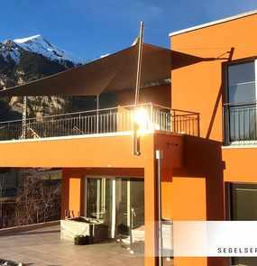 Ein rollbares Sonnensegel über der Terrasse und dem Pool eines Wohnhauses