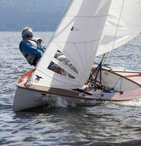 Zwei Segler lehnen sich aus dem Boot um das Gleichgewicht zu halten