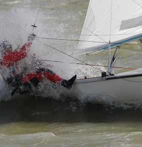 Ein Segler lehnt sich aus dem Boot um das Gleichgewicht zu halten