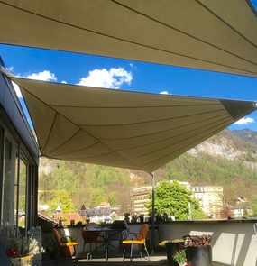Zwei rollbare Sonnensegel über der Balkonterrasse eines Wohnhauses