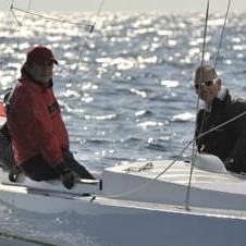 Drei Segler auf Ihrem Segelboot mit der ungarischen Flagge