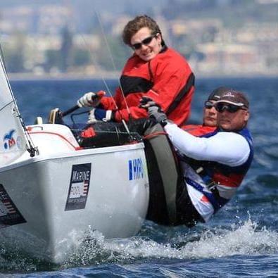 Drei Segler lehnen sich auf der Backbordseite aus dem Segelboot um das Gleichgewicht zu halten
