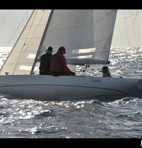 Ein Segelboot mir drei Seglern fährt über das Wasser.