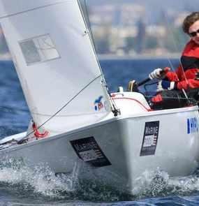 Ein Team aus drei Seglern lehnt sich aus dem Boot um das Gleichgewicht zu halten