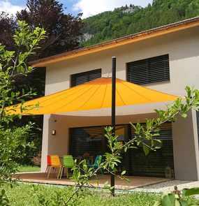 Ein Sonnensegel über der Terrasse eines Wohnhauses