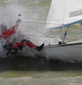 Ein Segler lehnt sich auf der Steuerbordseite aus dem Segelboot um das Gleichgewicht zu halten