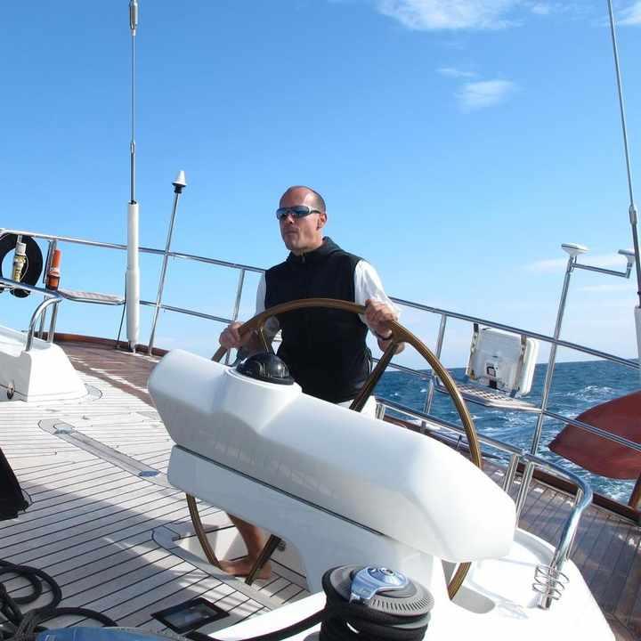 Klaus Theimer am Steuerrad eines Segelschiffes. Im Hintergrund ein großes Gewässer und der Himmel.