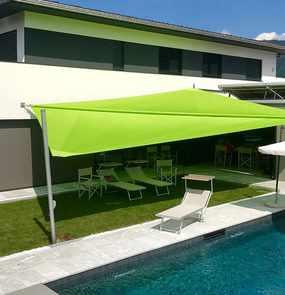 Ein rollbares Sonnensegel über den Sonnenliegen an einem Pool eines Wohnhauses.