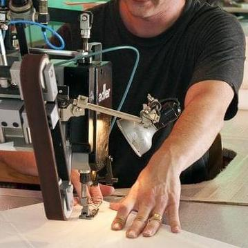Ein Segelmacher vernäht die Ecke eines Segels