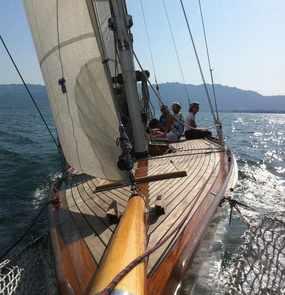 Die Kamera ist am Bug des Segelbootes befestigt. Sie zeigt drei Personen auf dem Deck.