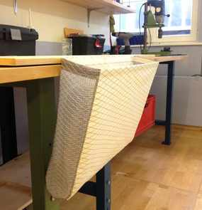 Eine Schotentasche hängt an einer Werkbank