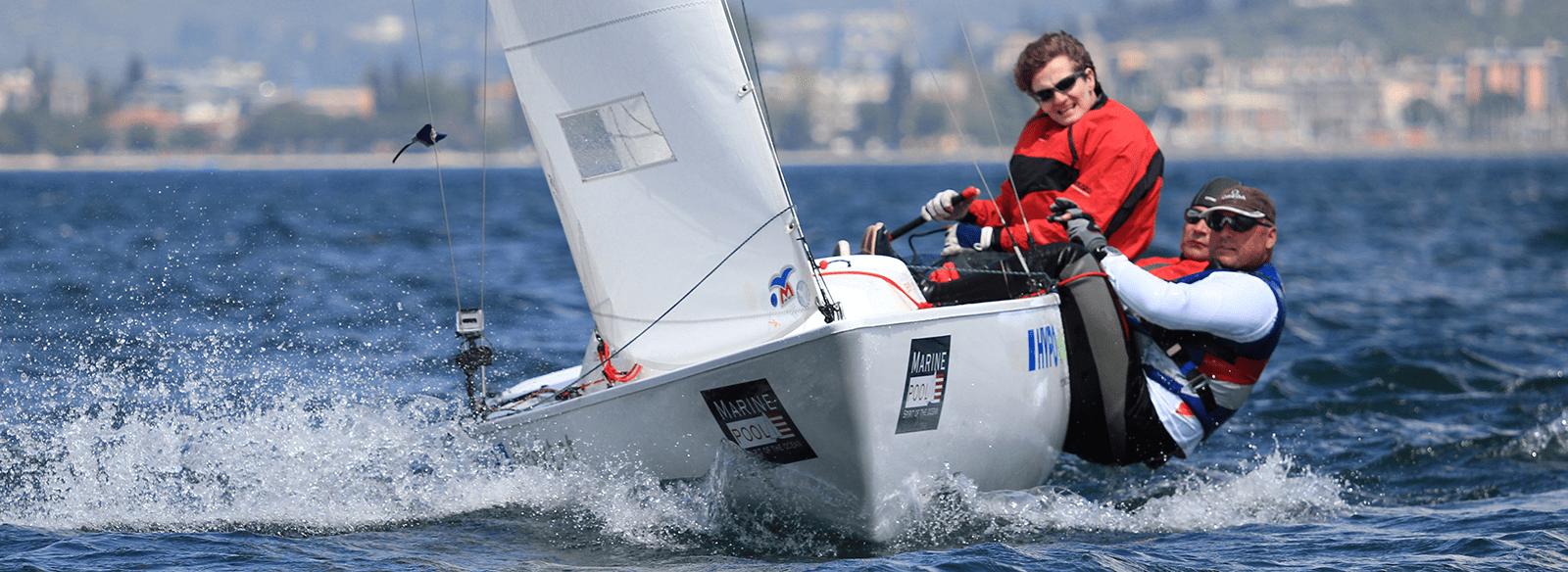 Ein Team aus drei Seglern lehnt sich von einem Segelboot um das Gleichgewicht zu halten