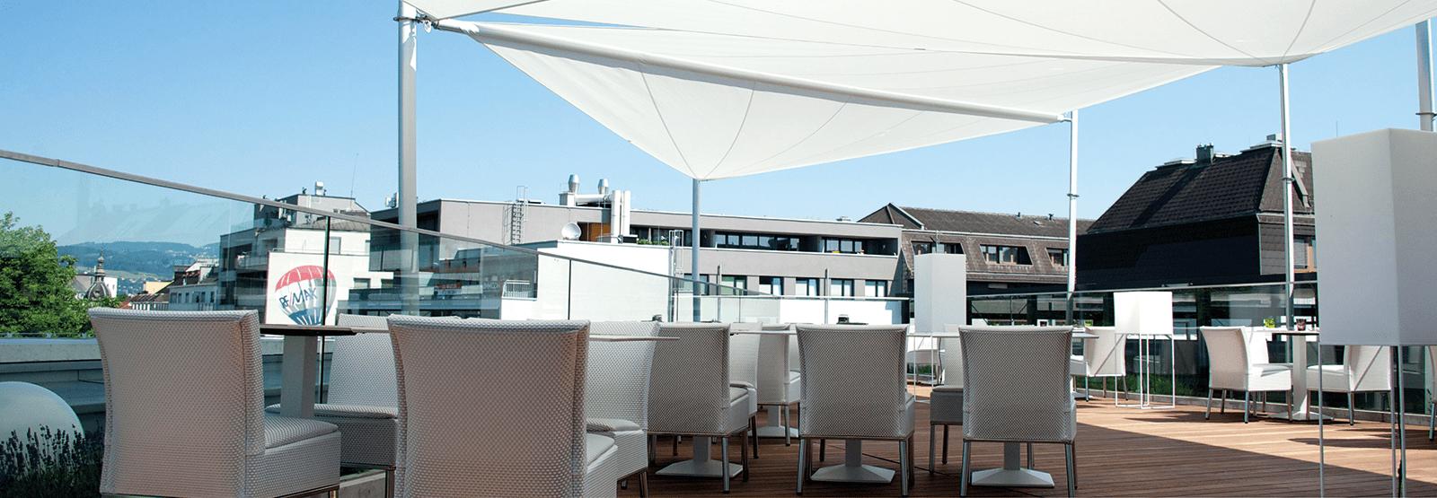 Eine möblierte Dachterrasse im Schatten eines Sonnensegels