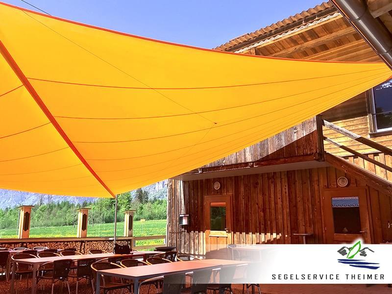 Gelbes aufrollbares Sonnensegel in einem Biergarten