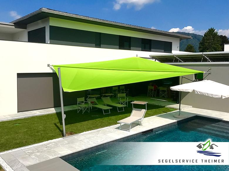 Ein Sonnensegel über der Terrasse eines Wohnhauses. Daneben befindet sich ein Pool.